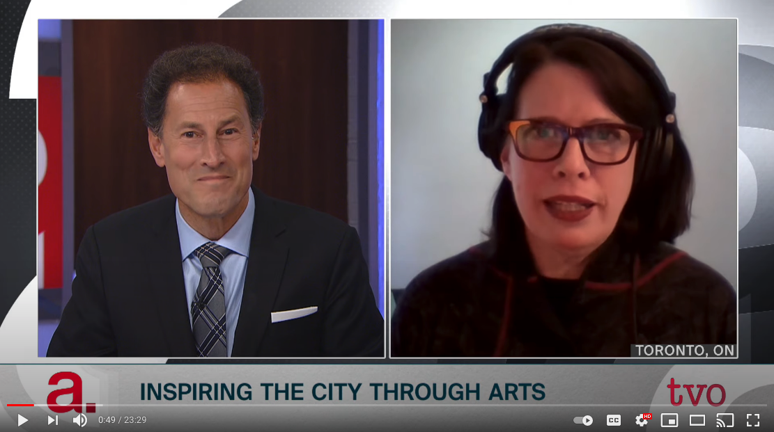 Screen capture of a YouTube video displaying a side-by-side split screen of a caucasian man, Steve Paikin, on the left side and a caucasian woman, Celia Smith on the right. Both are directly facing the camera and are engaging in a video call with each other. Steve Paikin has short dark hair and is wearing a dark dress jacket, light blue dress shirt, and a grey tie with a black and white cross stripe patter. Celia Smith has shoulder length brown hair, is wearing glasses, and is wearing a dark reddish brown shirt. Below the camera feed is the title, Inspiring the city through arts, and the TVO logo is on the lower right corner of the screen. The Agenda logo is on the lower left corner of the screen.