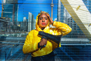 Exterior day-time photograph of a dark-skinned woman, Khadijah Roberts-Abdullah, holding a megaphone with her right hand across her chest, wearing a yellow hooded sweatshirt and a crown on her head. Her left hand is placed on the left side of her head. She is standing in front of a metal fence with downtown Toronto and the C N Tower in the background.