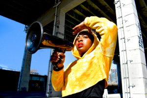 Exterior day-time photograph of a dark-skinned woman, Khadijah Roberts-Abdullah, holding a megaphone in front of her mouth with her right hand. Her left hand is shielding the sun from her eyes. She is wearing a yellow hooded sweatshirt and a crown on her head. She is standing under the Gardner Expressway bridge in Toronto, specifically at The Bentway.
