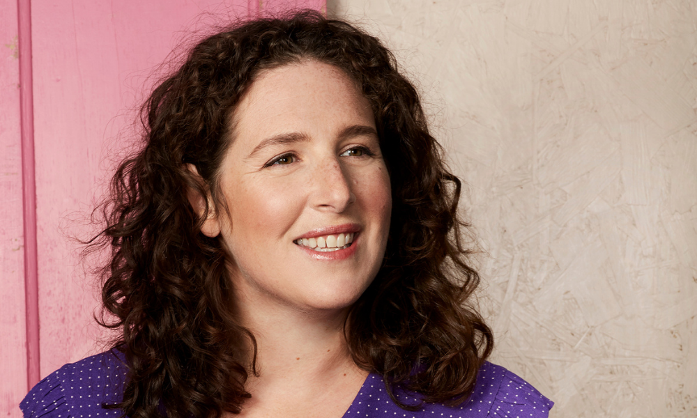Portrait of a caucasian woman, Jessica Litwin, on a wooden background half painted pink and half pained beige. She is looking to the left of the camera smiling. She has brown wavy hair that comes just past her shoulders and is wearing a purple shirt with small white dots.