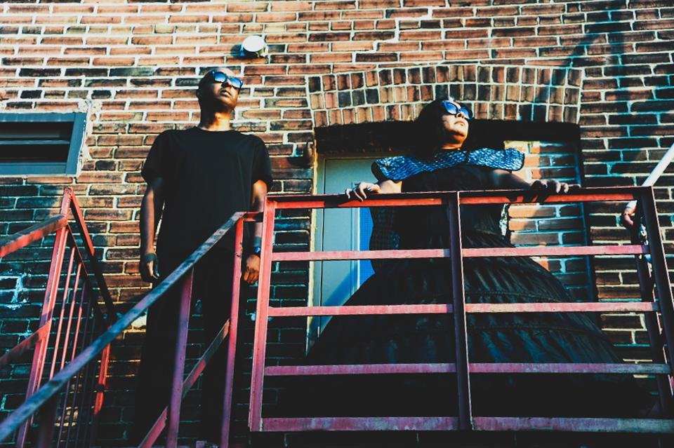 Exterior daytime photograph of two figures standing on top of a fire escape with a brown brick building behind them. The figure on the left has no hair and is wearing black sunglasses, a black t-shirt and black pants. The figure to the right has medium length black hair and is wearing black sunglasses and a large black hoop skirt.