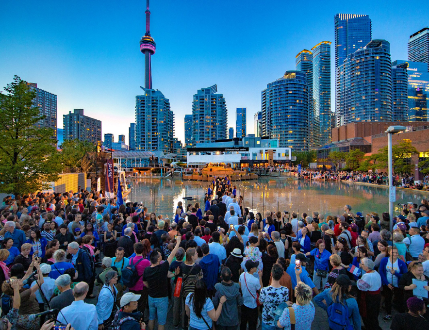 Luminato Festival Toronto crowd gathered for a performance in front of the CN Tower at dusk.