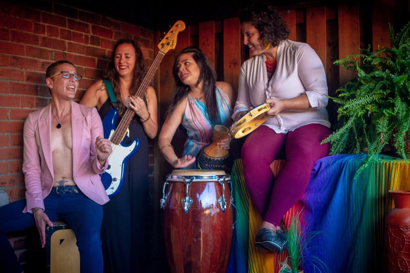 Baobá. A group of 4 women with instruments gathered together smiling and singing.