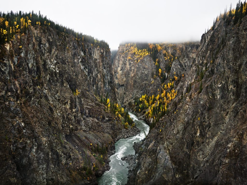 A photo of the Stikine River in Northern British Columbia taken by Edward Burtynsky. A river flows through two rocky mountains. The mountains have slight vegetation on them with yellow coloured trees. Clouds partly cover the top of the mountains. The river appears to be flowing rapidly and strongly in between the mountains.
