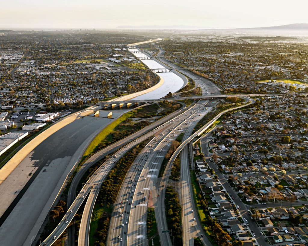 Header image for In the Wake of Progress showing a vast river and highway in the daytime.
