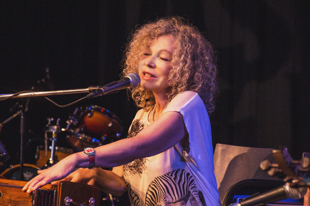 Lenka Lichtenberg. Lenka is wearing a white tshirt and singing into a microphone. Lenka has shoulder length, curly blonde hair.