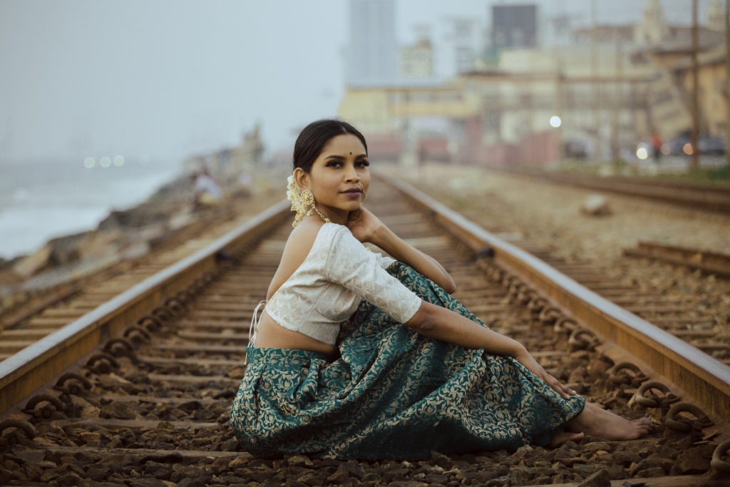 Navz-47. Navz is seated on train tracks and looking at the camera in profile. Navz is wearing a long green skirt and a white shortsleeved top.