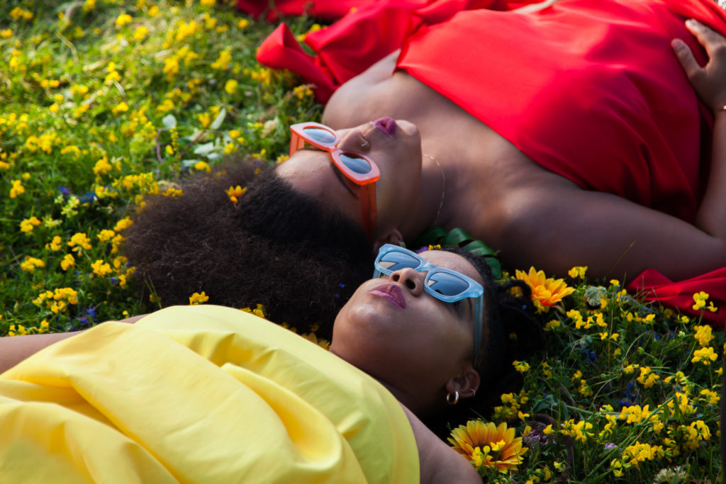 OKAN. Two women laying in the grass with their heads next to one another and their bodies facing opposite directions. One woman is wearing a red dress and the other is wearing a yellow dress. Both are wearing sunglasses.