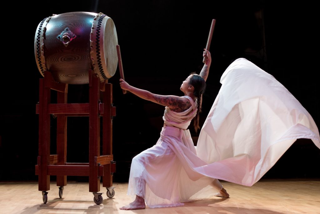 Raging Asian Women Taiko. A woman in a billowing white dress drums on a large drum mounted on a scaffold. The woman is in profile with drum sticks in both hands.