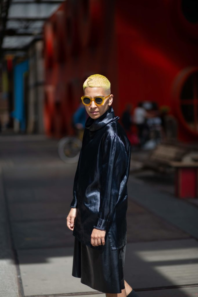Säye Skye. Säye is wearing a black leather trenchcoat and skirt and looking at the camera over their left shoulder. Säye has short blond hair and is wearing dark sunglasses. Säye is standing in an alley with a red wall behind them.