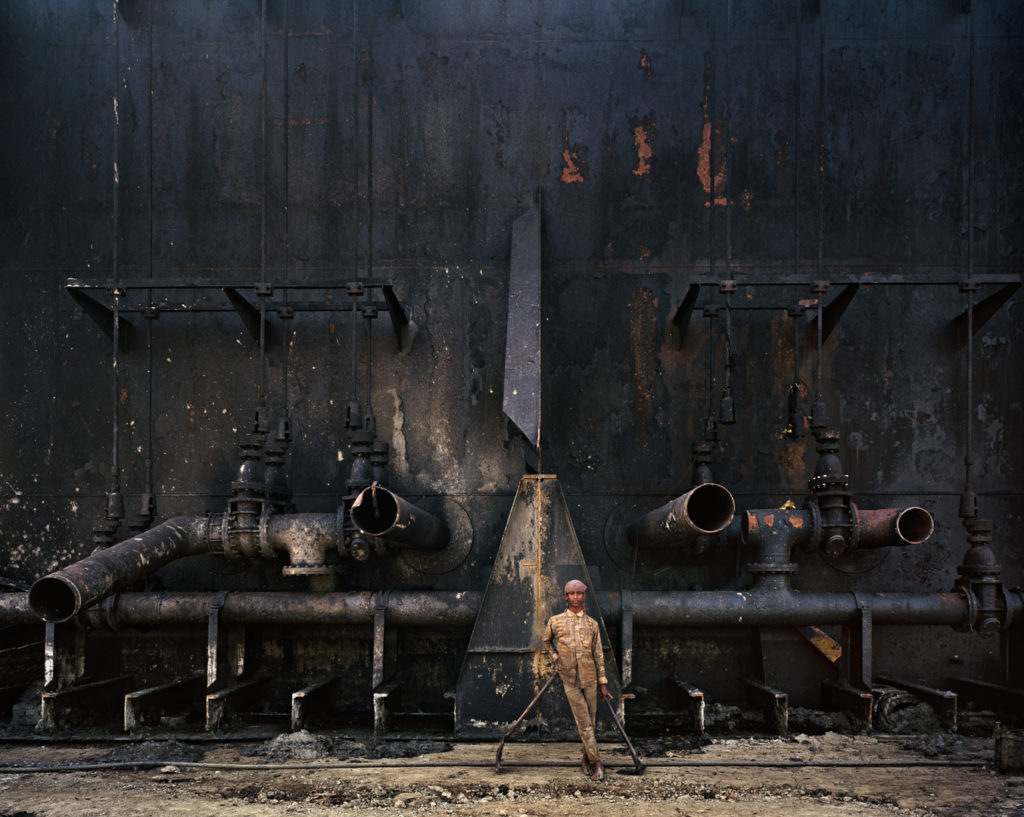 A boy stands in front of a large metal ship. He is working on the process of shipbreaking. He is holding two axes and is wearing a dirty, beige jacket and beige pants. He is barefoot, and his feet are covered with ashes.
