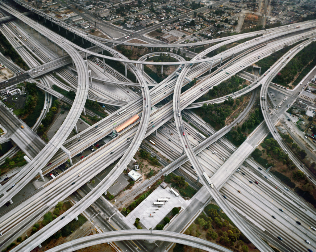 An aerial photo of a highway intersection taken by Edward Burtynsky. This is a bird's eye view of highway lanes winding over each other. Cars and trucks are driving in the many lanes pictured here.