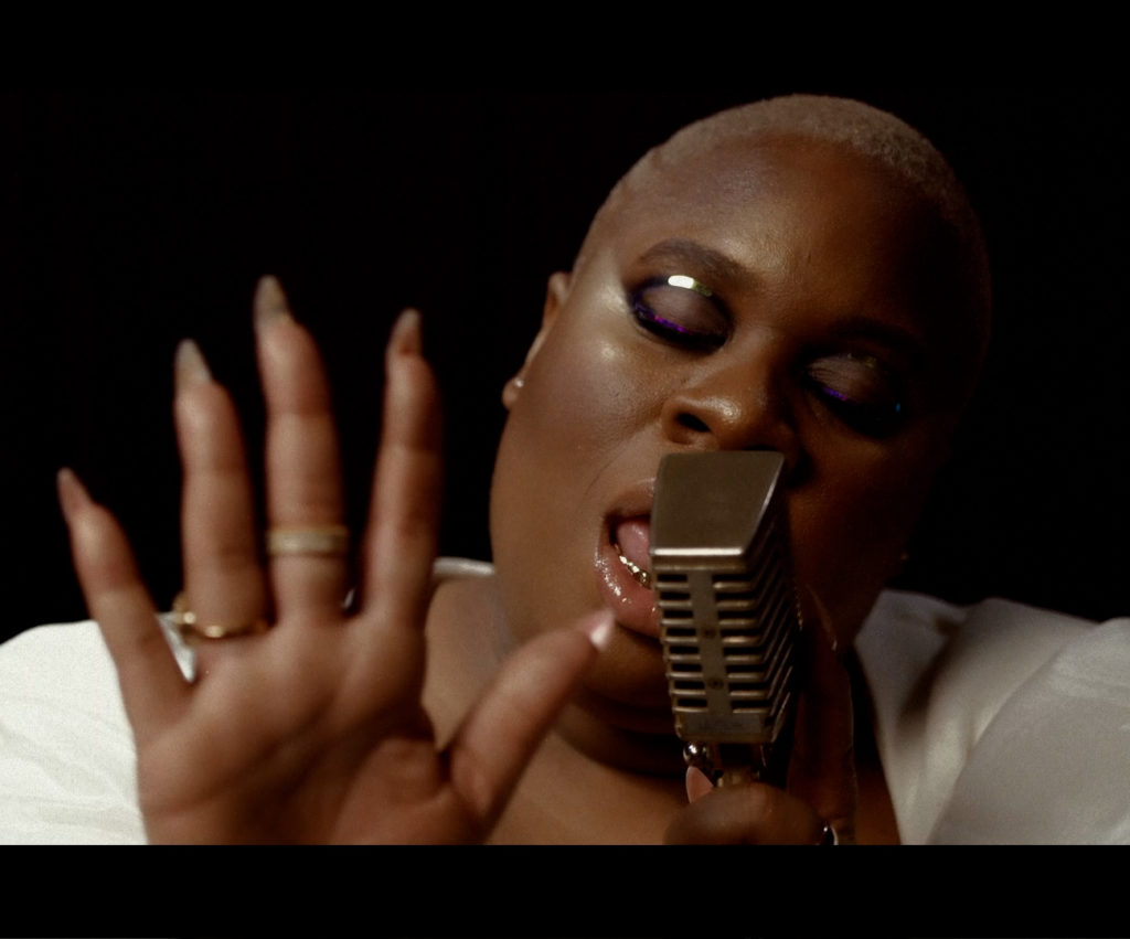 TiKA the Creator facing the camera and singing passionately into a microphone. TiKA is black with short white hair. TiKA's hand is raised and facing the camera palm forward. TiKA is wearing a white top and is in front of a black background.