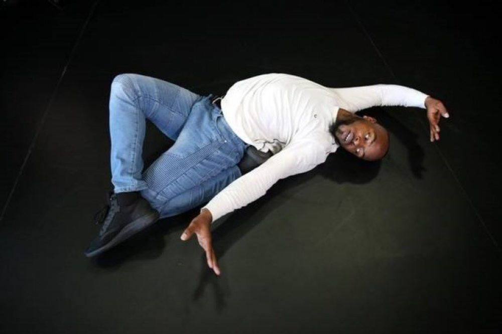 The Toronto Kiki Ballroom Alliance. Image of dancer in twisted dance move with right arm overhead. The dancer is wearing a white long-sleeved shirt, jeans, and black sneakers.