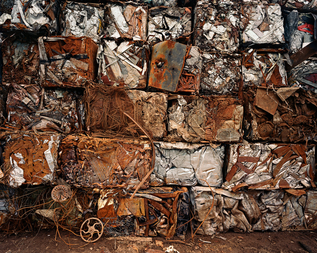 An image of rusty metal molded together, taken by Edward Burtynsky. The scrap metal is tightly packed together in cubes placed on top of each other, forming a rusty wall of metal.