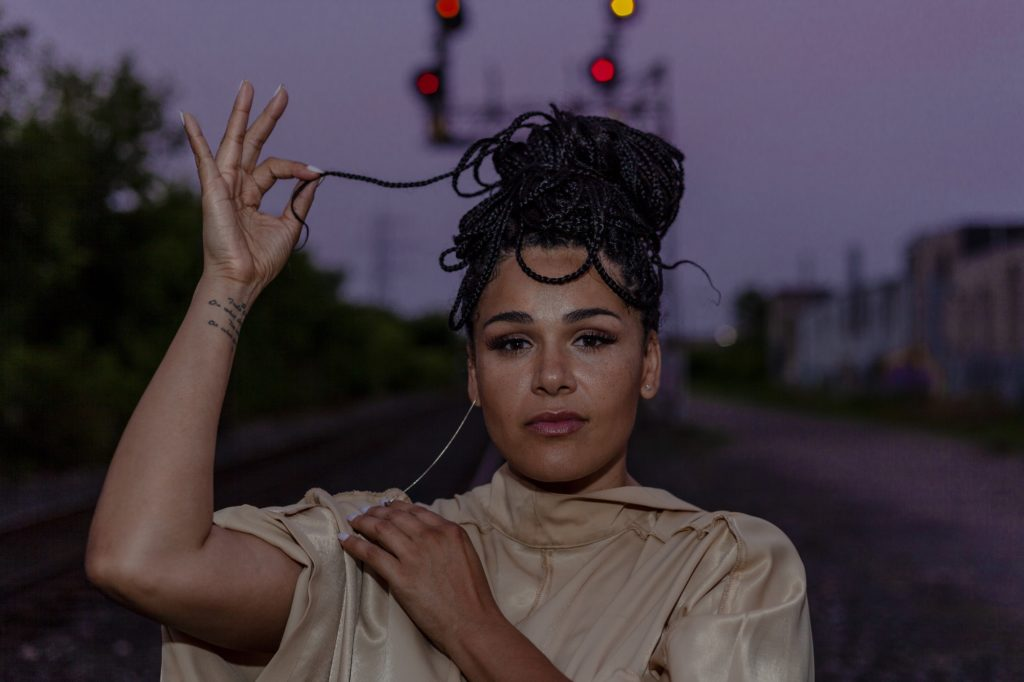 Zaki Ibrahim has black braided hair in an up-do. Zaki is facing the camera and holding one braid away from her head with her right hand. Zaki is wearing a beige top and has her left hand across her chest.