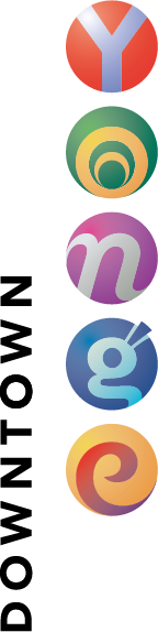 The Downtown Yonge BIA logo has the word downtown in simple black text placed vertically next to the word Yonge. The letters of the word Yonge are individually rendered in stylized multicoloured circles.