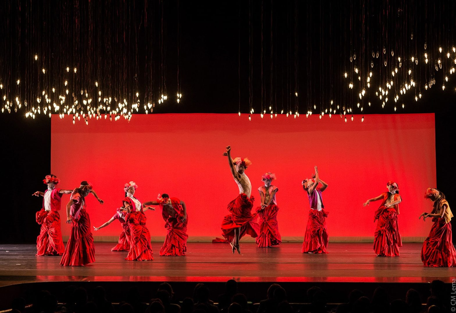 A group of dancers are performing on stage in red dresses. There is a red backdrop on the stage behind them. Orange lights are strung up on the ceiling and hanging above them.