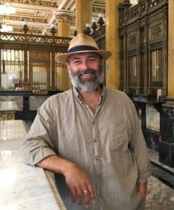 Standing in an ornate art nouveau post office, a middle-aged white man with dark brown eyes, a greying beard, and straw fedora faces us and smiles, leaning against a white marble countertop.