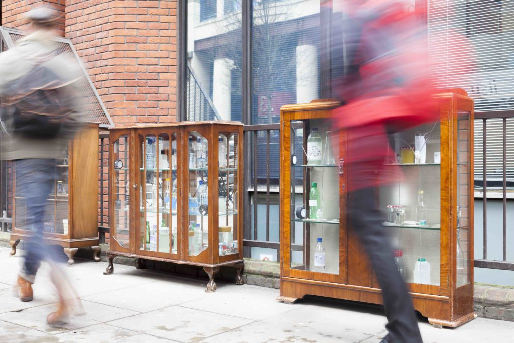 Wooden cabinets of glass doors holding bottles of water on the sidewalk in London, England.