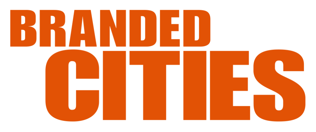 The Branded Cities logo is orange bold font in all caps on a white background. The word Branded sits above and to the left of the word cities, which is bigger in height.