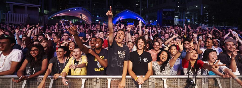 Photo of the audience at The Roots' performance during Luminato 2014. A large crowd of people are cheering and smiling at a live concert.