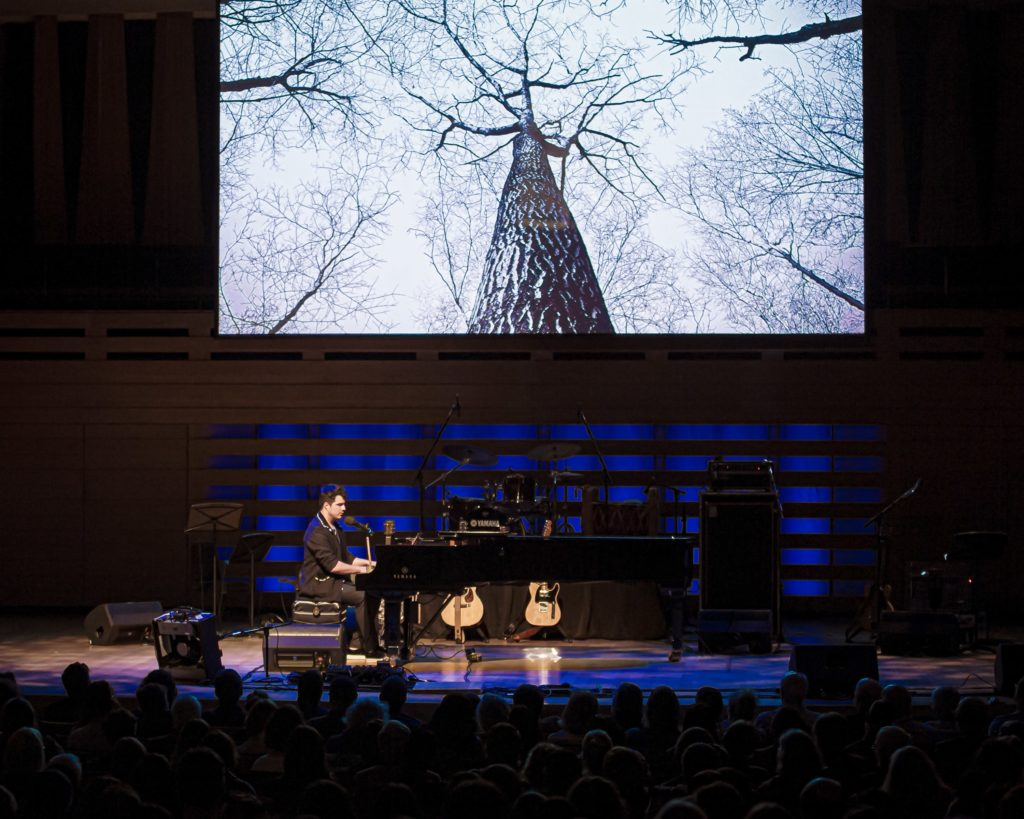 Jeremy Dutcher, a musician, composer, and vocalist is sitting at a grand piano performing at a concert hall. There is a projection behind him of a black and white image of a forest.