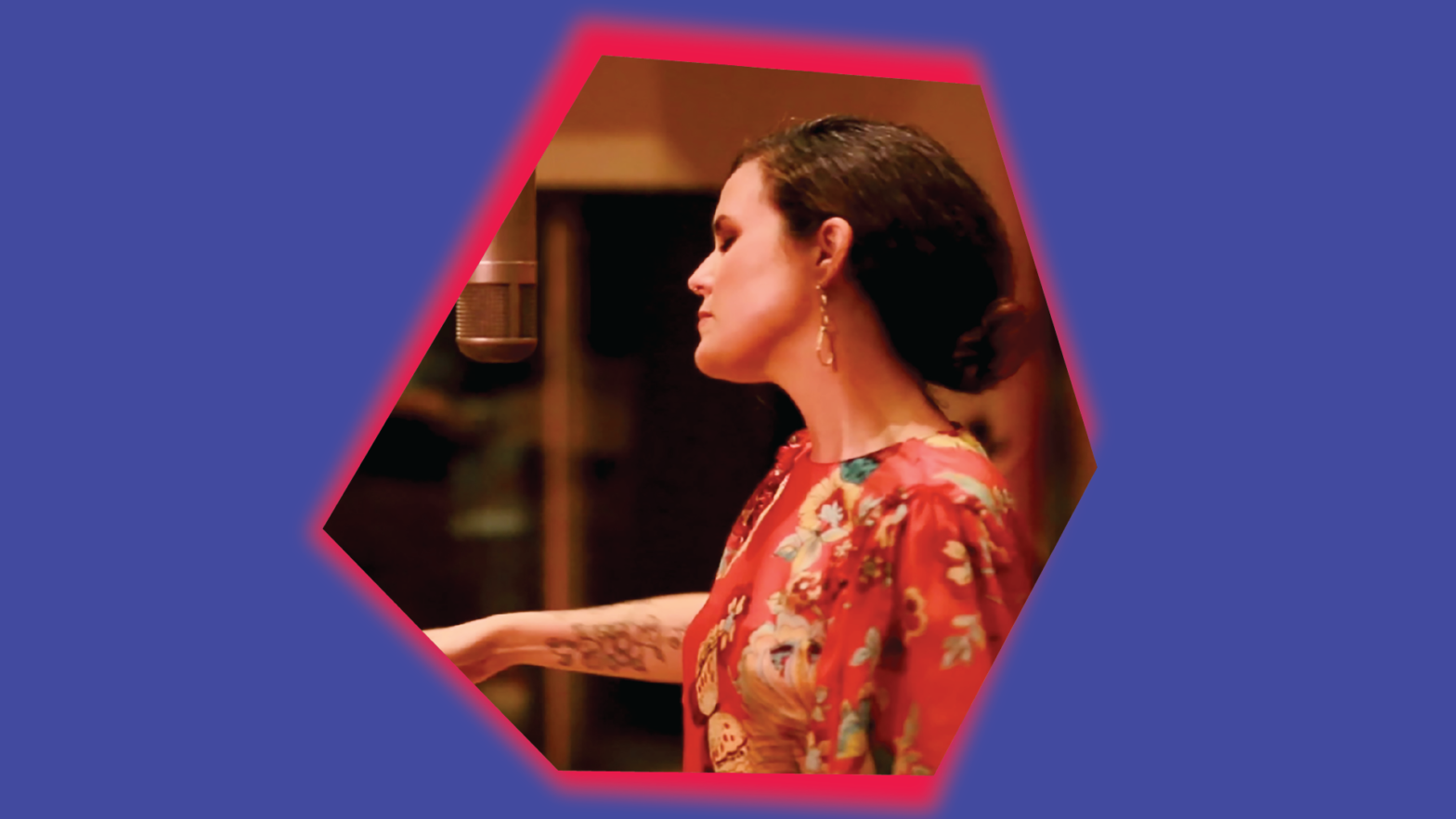Photo of singer iskwe singing in the studio. Her photo is embedded within a rhombus asymmetrical shape with a pink glow behind it on top of a purple background.