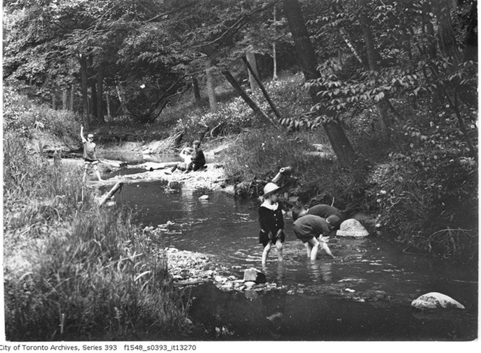 Green background with asymetrical shape iBlack and white archival image of children playing in a creek.