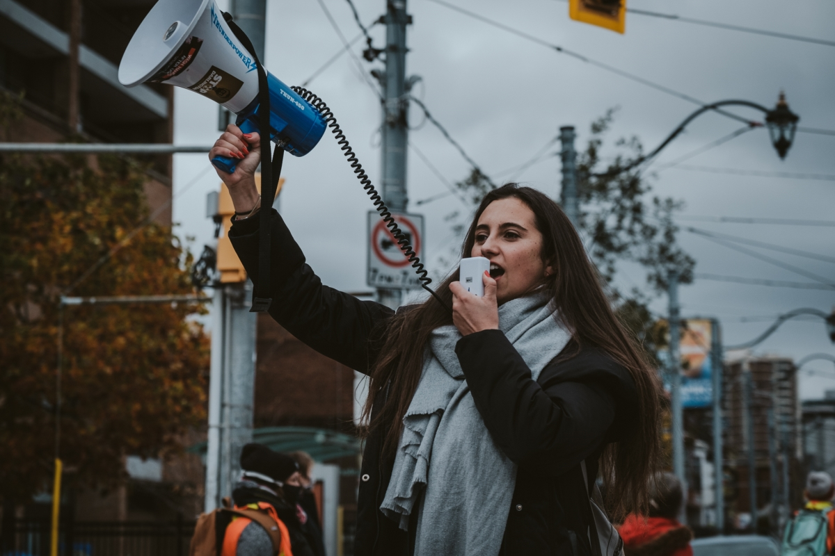 Allie Rougeot at a protest and speaking into a megaphone.