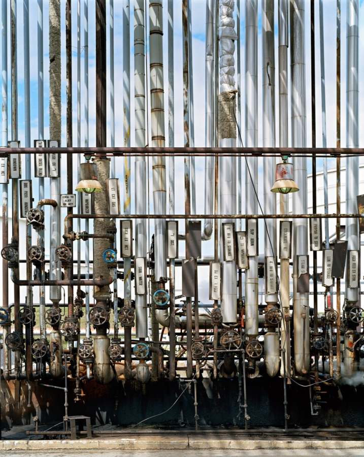 Edward Burtynsky's Oil Refinery is a wall of pipes lined up vertically with the blue sky showing between the pipes.