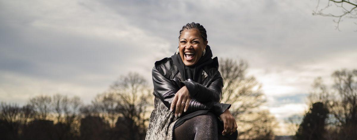 Image of Measha Brueffergosman sitting on a picnic table and smiling big at the camera.