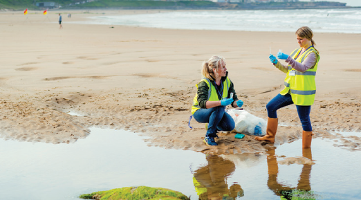 Image of two people wearing safety vests on a beach doing scientific work.