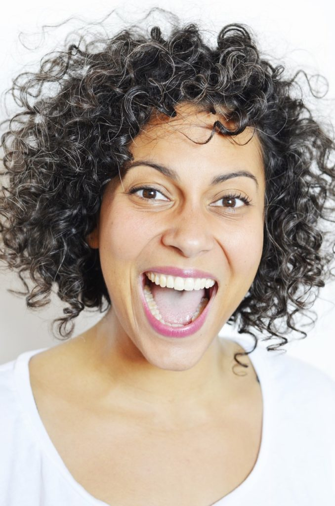 Headshot of Liza Paul. She is smiling joyfully and wearing a white t-shirt against a white backdrop.