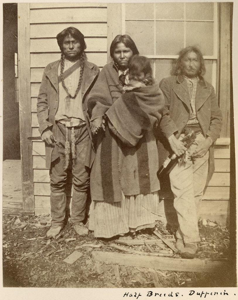 A sepia tone photo of 3 unidentified Metis people and a baby posed in front of a building at Dufferin
