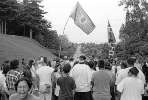 Banner image. Back view of marching crowd holding Mohawk Warrior Society and Hiawatha Belt flags on street