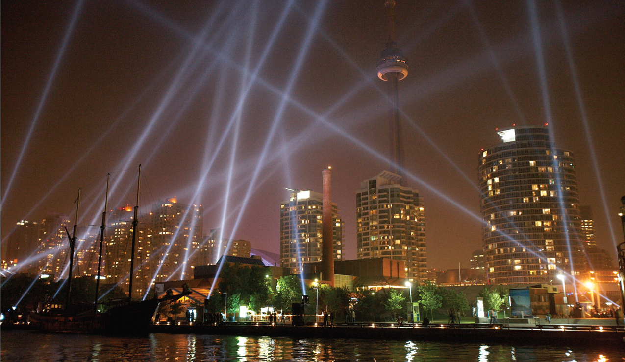 Banner image for St Joseph Communications shows the Toronto skyline with spotlights criss-crossing infront of the CN Tower.