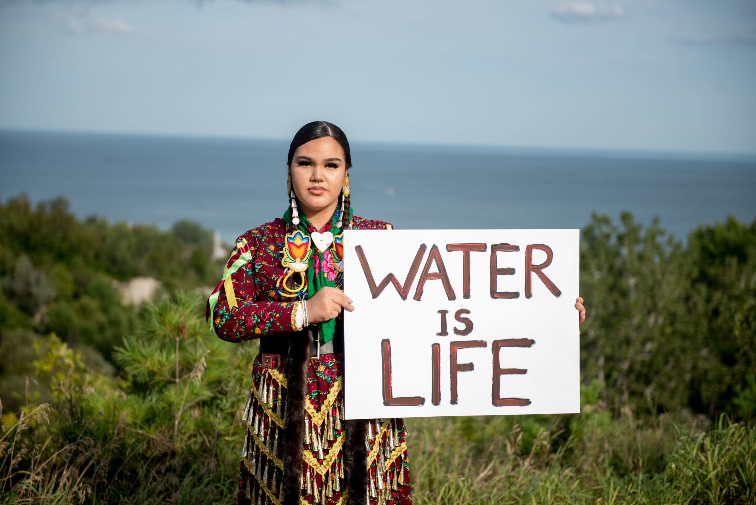 Image of Indigenous woman Emily Dick holding a sign saying Water is Life